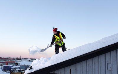 Professionell snöskottare röjer snö från tak