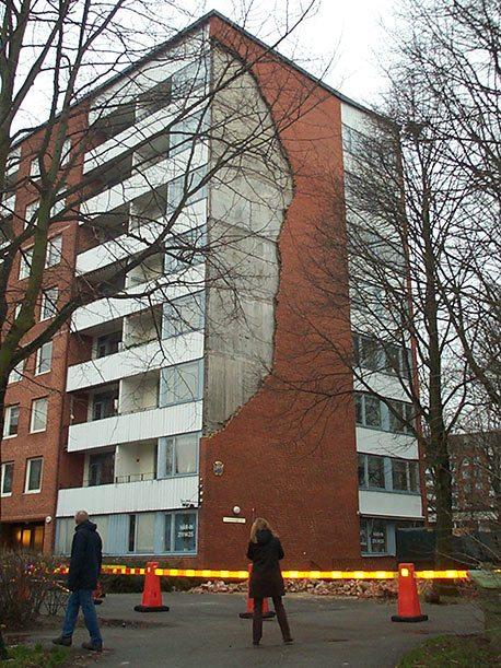 Höghus där en stor del av tegelfasaden har rasat