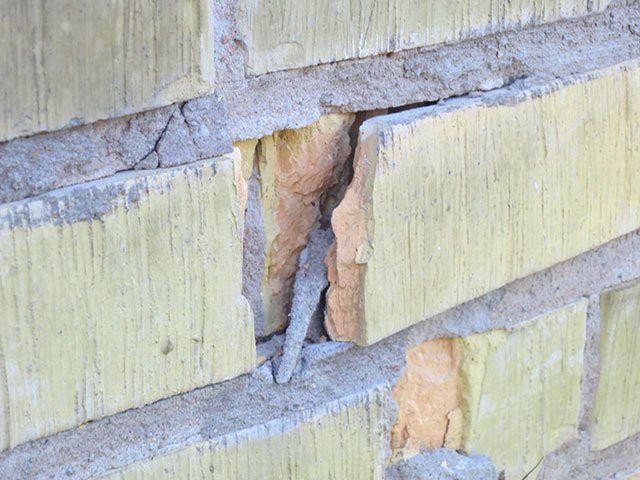 En del av en tegelsten på en gul tegelfasad har spruckit loss