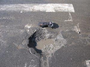 Ett vattenfyllt potthål i asfalten