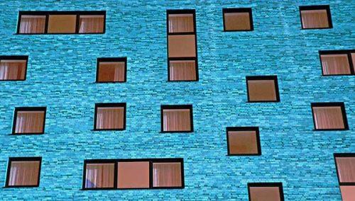 Asymetriskt placerade fönster på en blå fasad